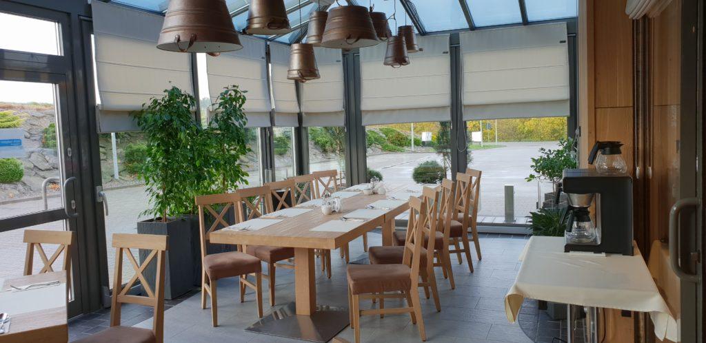 Beżowe rolety rzymskie wiszące na dużych oknach w restauracji
