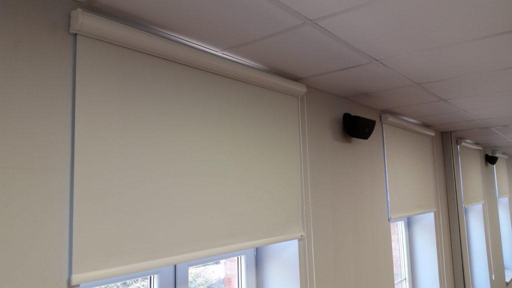 Białe rolety wolnowiszące z zaciemniającą tkaniną w sali konferencyjnej