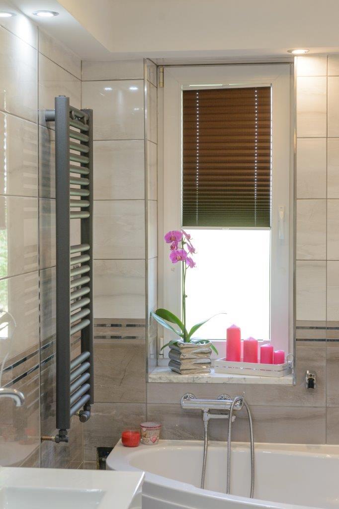Zdjęcie pokazuje ciemnoczerwoną roletę plisowaną zamontowaną w łazience