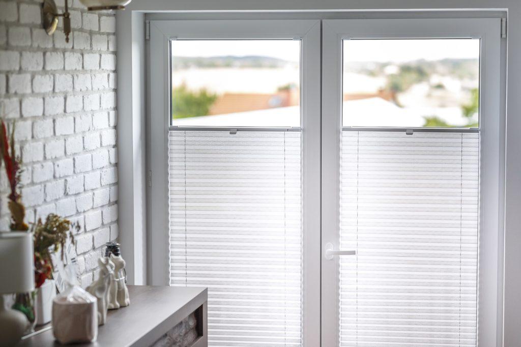 Zdjęcie pokazuje białe plisy założone na oknie balkonowym w białym pokoju