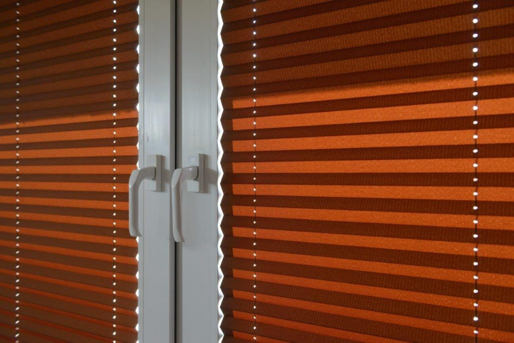 Obrazek pokazuje czerwony materiał plisowany zawieszony na oknie