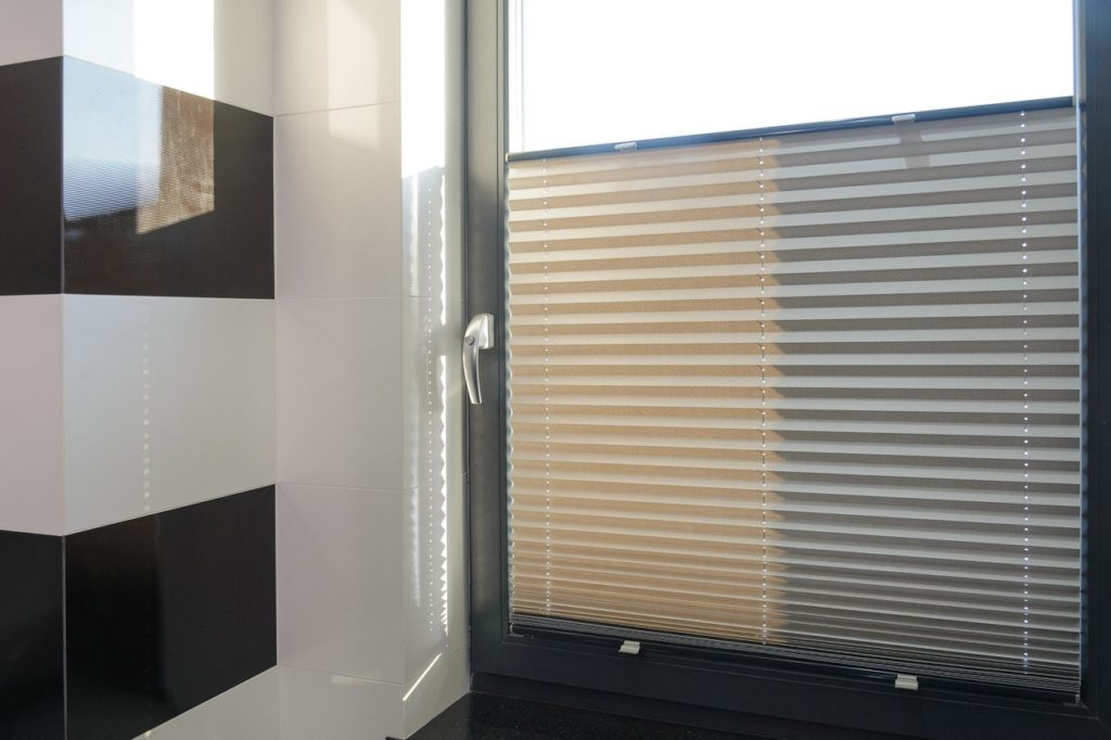 Zdjęcie przedstawia jasną plisę zainstalowaną na czarnym oknie