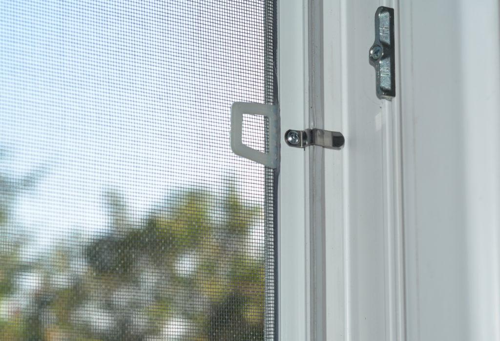 Na zdjęciu zamontowana na białym oknie moskitiera w białej ramce