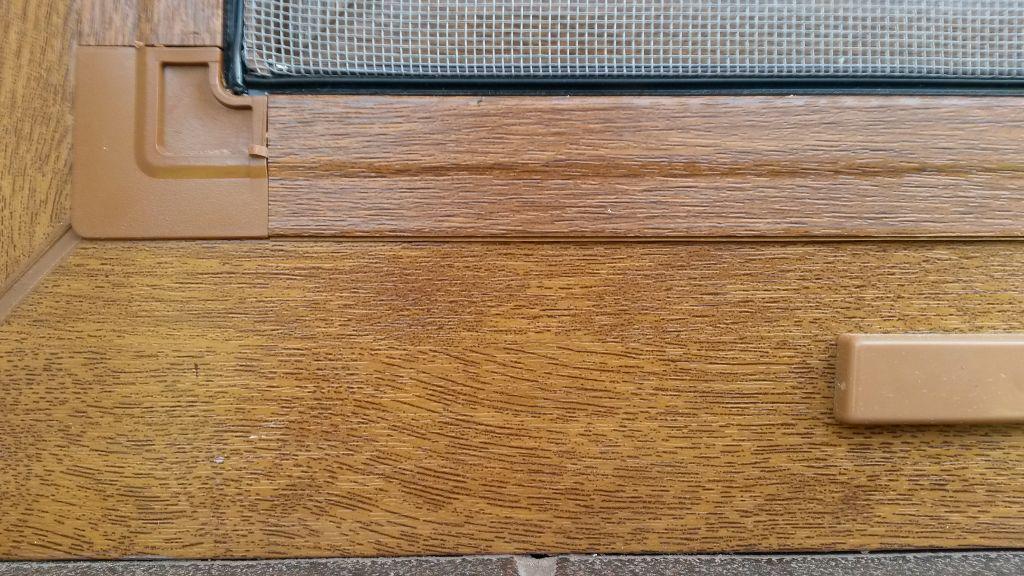 zdjęcie imitujących drewno okna i moskitiery